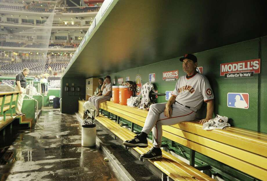 Giants manager Bruce Bochy (right) waits out a weather delay in the dugout before a game against the Washington Nationals in Washington in 2009. Bruce Bochy grew up in Falls Church, Va., and his father took Bruce to his first baseball game at RFK Stadium to watch the Washington Senators play the Cleveland Indians. Photo: Nick Wass / Associated Press 2009 / FR67404 AP