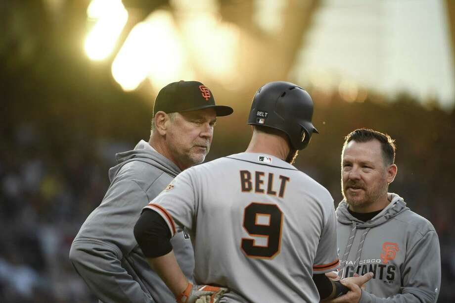 Bochy and a trainer look at Brandon Belt after he was hit with a pitch during the fourth inning against the San Diego Padres at Petco Park on Opening Day. Photo: Denis Poroy / Getty Images / 2019 Getty Images