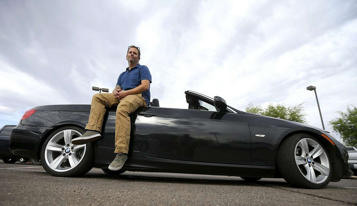 In this April 23, 2019, photo, Chris Williamson poses for a photo sitting on his car in Phoenix. When Williamson was in the market for a new family car, a timely ad and conversations with a co-worker convinced him to try something out of the ordinary. He bought the BMW 3 Series convertible and covers the payments by renting it to strangers on a peer-to-peer car sharing app called Turo. It allows his family of seven to have a nicer car, essentially for free. (AP Photo/Ross D. Franklin)