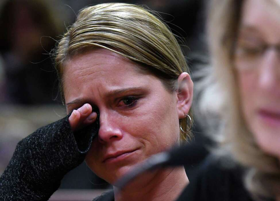 Kim Steenburg wipes away tears during the State Standing Committee on Transportation hearing on