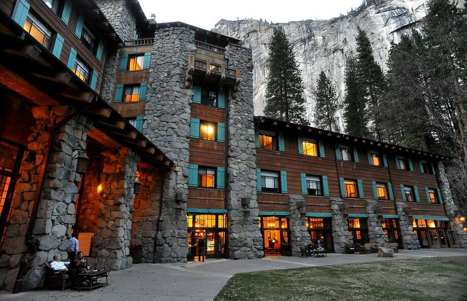 In this March 24, 2014 file photo, the historic Ahwahnee Hotel is lit up as dusk falls over Yosemite Valley, in Yosemite, Calif. The names of iconic hotels and other facilities in the world-famous Yosemite National Park change back after battle over who owns the intellectual property. Photo: John Walker / Associated Press