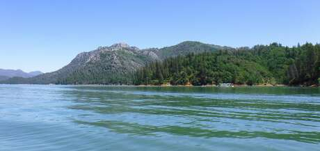 A houseboat cruises across the lower McCloud arm of Shasta Lake, one of hundreds of recreation lakes in California filling for Memorial Day Weekend