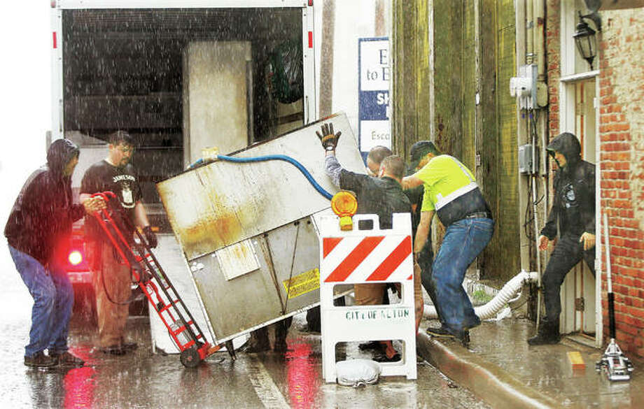 In the midst of a downpour, which will only make things worse, employees of Morrison's Irish Pub at the corner of West Broadway and State Street in Alton were moving out their kitchen equipment Thursday after forecasters announced Mississippi River floodwaters will reach the fifth-highest level by early next week. The river forecast is holding at 35.5 feet, several feet higher than just a few weeks ago, and at the same level that caused the Melvin Price Locks and Dam 26 in Alton to close during the Great Flood of 1993. West Alton, Missouri, businesses and residents are also packing up with the likelihood their levee will be topped and the town flooded this weekend.