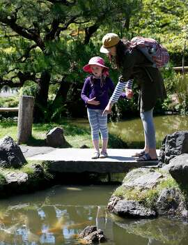 San Franciscans Nora Curnyn, 5, and her mother Elena Curnyn observe the koi in the main pond of the Japanese Tea Garden at Golden Gate Park in San Francisco, Calif. on Thursday, May 2, 2019. The Recreation and Parks Commission is considering an increase to entry fees to address much needed repairs and improvements.