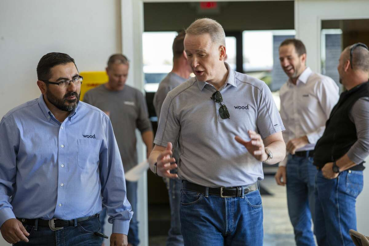 Robin Watson, chief executive officer of Wood plc, right, talks with employee Marcos Ortiz, while Andrew Stewart, CEO, Americas, in the background at right, talks with other employees during a recent visit to Seminole.
