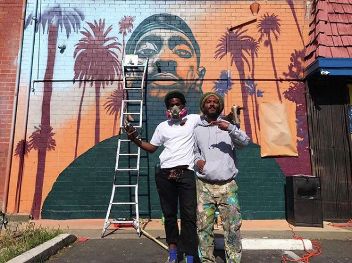 Artists Timothy B and Natty Rebel pose in front of their new Nipsey Hussle mural in Oakland's Adams Point neighborhood.