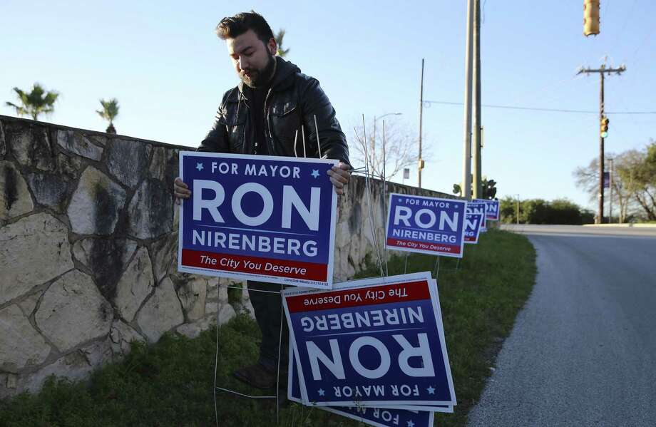 Campaign staffer Ben Guajardo places election signs outside Alamo Stadium where Mayor Ron Nirenberg announces his bid for re-election as city mayor with family and supporters Jan. 19. Photo: Kin Man Hui /San Antonio Express-News / ©2019 San Antonio Express-News