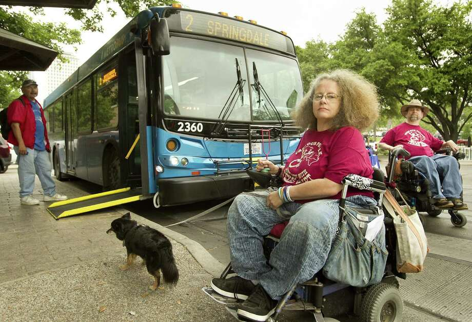 Stephanie Thomas and her support dog Boots Templeton, along with Gene Rodgers, right, are about to board a bus that is ramp-equipped April 24, 2014 in Austin. Thomas and Rodgers were among those who attended a protest at the state Capitol geared toward gaining improved access. Local government lacks representation of disabled with only one person representing the population. Photo: Laura Skelding /Associated Press / Austin American-Statesman