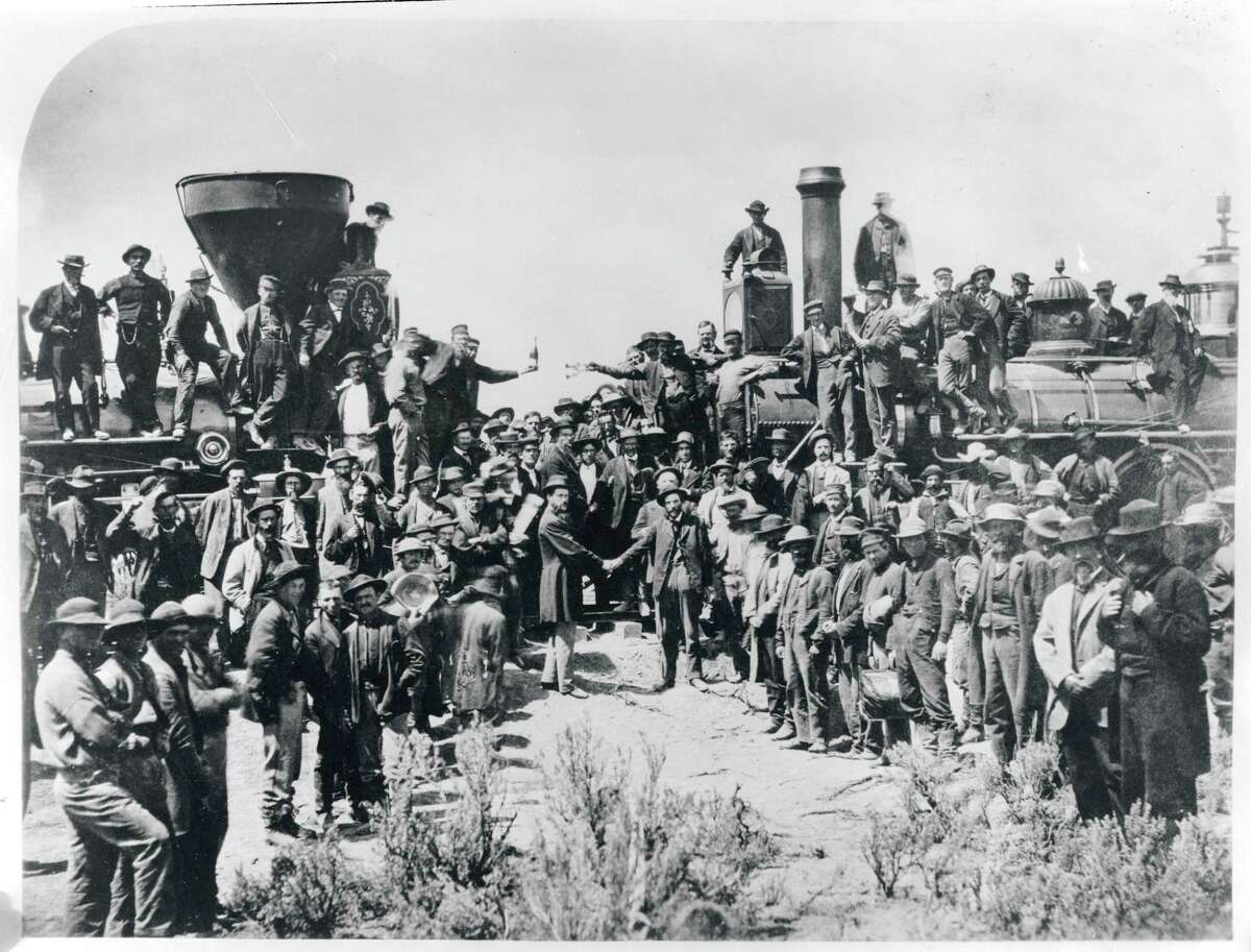 Railroad workers celebrate at the driving of the Golden Spike Ceremony in Utah on May 10, 1869 signifying completion of the first transcontinental railroad route created by joining the Central Pacific and Union Pacific Railroads.