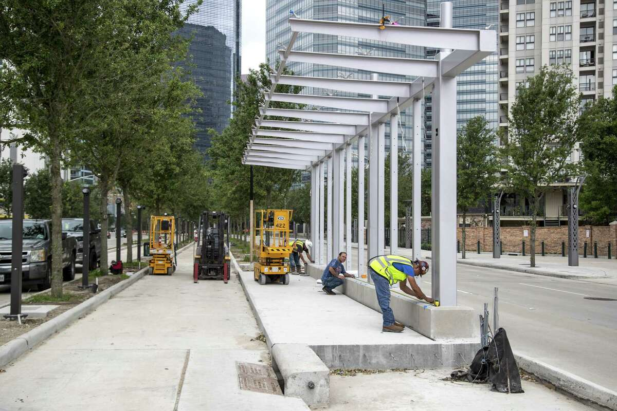 Construction workers erect a bus rapid transit station on Post Oak on April 30. Metropolitan Transit Authority officials are making a huge push toward bus rapid transit as part of a $7.5 billion transit plan.