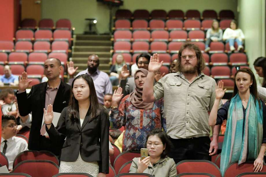 New citizens stand to take the Oath of Allegiance during a naturalization ceremony at Tamarac High School on Thursday, May 2, 2019, in Brunswick, N.Y.  (Paul Buckowski/Times Union) Photo: Paul Buckowski / (Paul Buckowski/Times Union)