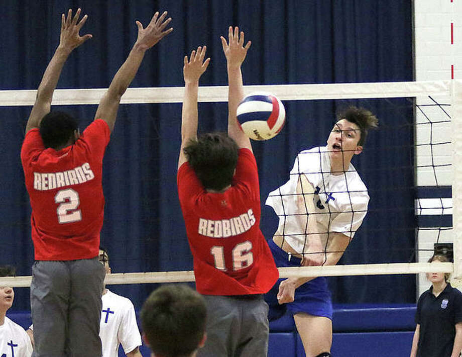 Marquette Catholic sophomore Jake Roth (right) hits past Alton's block for a kill against the redbirds' Donnel Craig (2) and Van Hill (16) in the first set of the Explorers' three-set junior varsity victory over Alton on Thursday at Marquette High School in Alton. Photo: Greg Shashack | The Telegraph