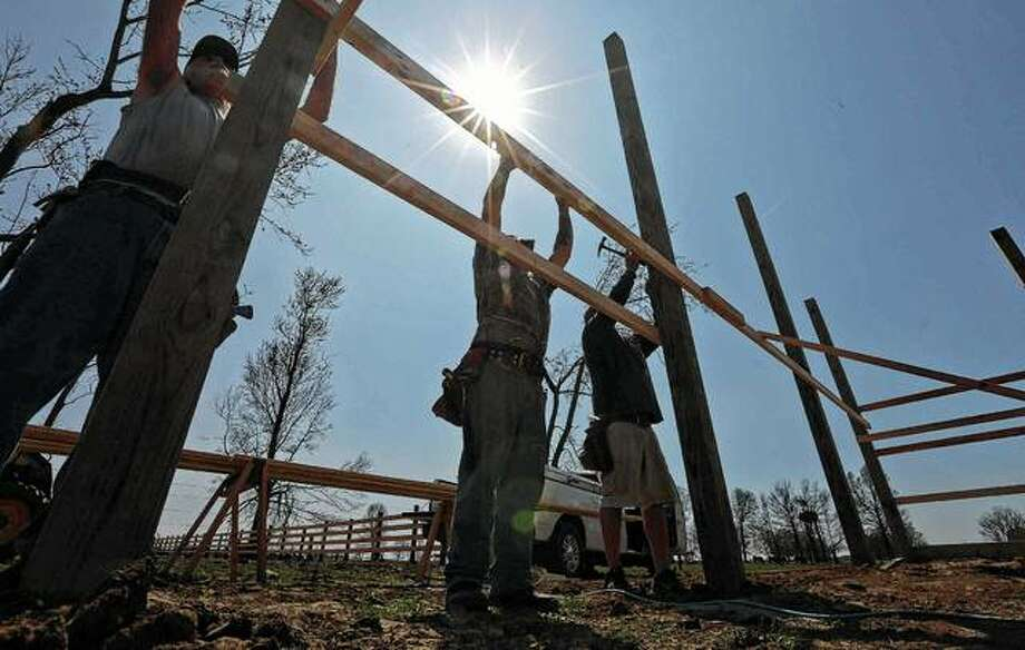 Lyle Prosser Construction employees work in April on a house that was destroyed in December by a tornado in Taylorville. Photo: Clay Jackson | Herald & Review Via AP