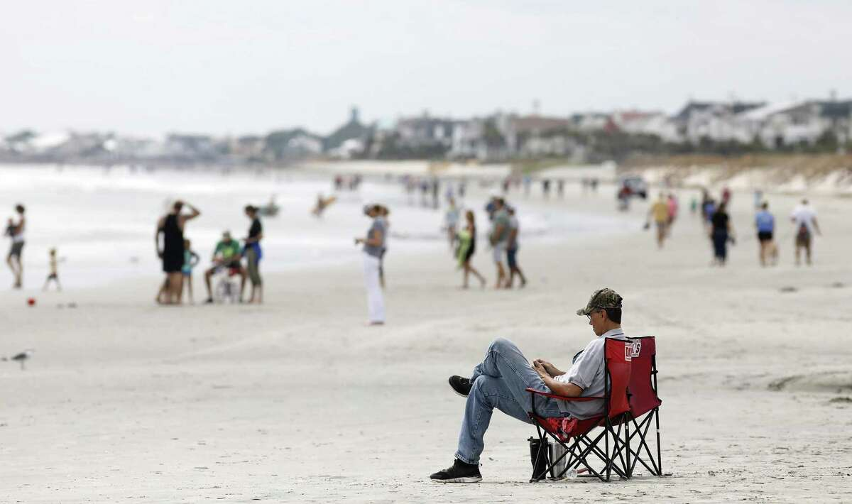 Beach goers hang out at the Isle of Palms, S.C. President Donald Trump's plans to open the Atlantic coast to offshore drilling have run into political and legal roadblocks.