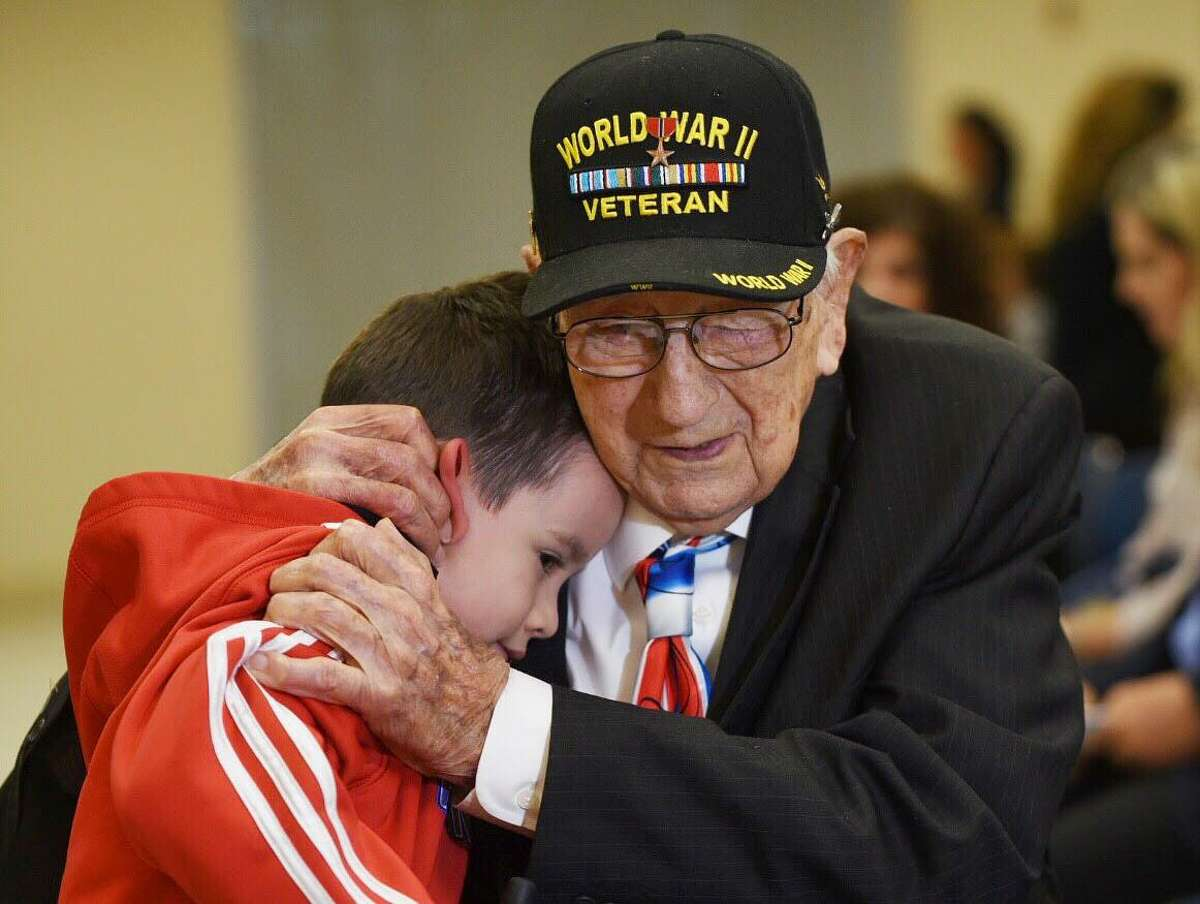 World War II Veteran John Valls hugs his great-grandson John Robert Ortiz Thursday, May 2, 2019, during an interview at the Joe A. Guerra Laredo Public Library before the Holocaust Remembrance Day ceremony.