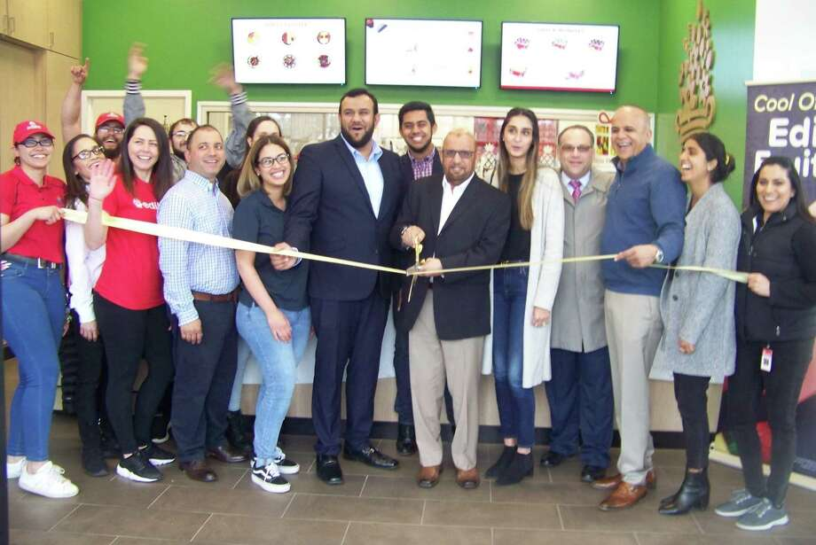 EDIBLE ARRANGEMENTS OPENS: From left, Ghulam Farid cuts the ribbon at the grand opening of Edible Arrangements at 1920 Dixwell Ave. in Hamden recently. To his right is Abdullah Farid, at center rear is owner Farrukh Farid, and to his left are Somia Farid, Quinnipiac Chamber of Commerce Business Development Executive Gary Ciarleglio, Edible Arrangements owner and founder Tariq Farid, Fatima Farid, and Edible Arrangements International VP of Compliance Sarju Patel. At left are members of the Edible Arrangements team. For information, visit www.ediblearrangments.com. Photo: Contributed Photo