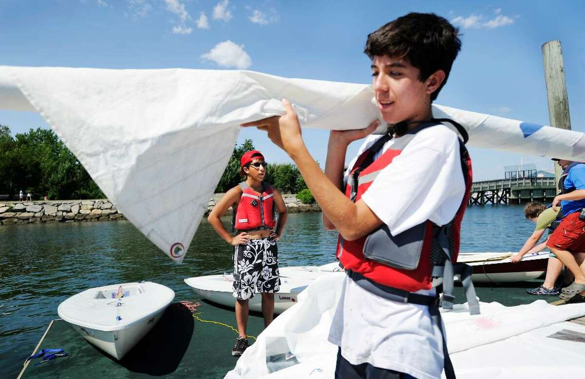 Andres Bastias, 15, carries a sail as Nick Gonzalez, 16, stands on the dock during the Young Mariners Foundation