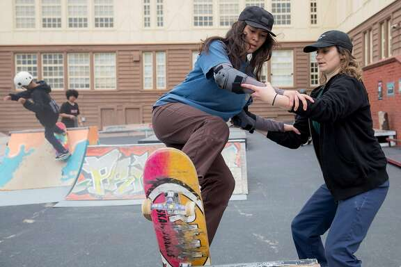 Skate Like a Girl volunteer Alexandra Pepin (right) assists Maryzelle Ungo, 21, while she practices dropping into a ramp during a skate clinic held by Skate Like a Girl at Playland at 43rd skate park in San Francisco, Calif., Saturday, April 13, 2019.