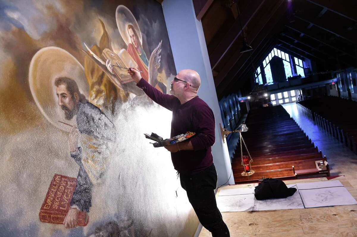 Paul Armesto of Queens, N.Y., paints the hands of St. John on an altar mural at Our Lady of Pompeii Church in East Haven recently, Working in oil, the painting, a four-month endeavor, depicts Our Lady of Pompei surrounded by Padre Pio, Mother Teresa, St. Clare, St. Vincent and other historical religious figures.