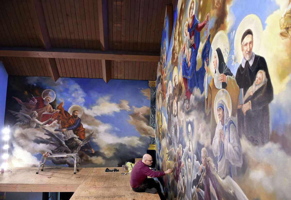 Paul Armesto of Queens, New York, paints the wings of an angel on an altar mural at Our Lady of Pompeii Church in East Haven on April 26, 2019 culminating four months of work on the project.