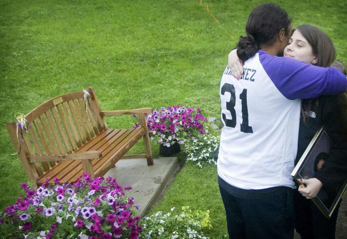 Lynette Martinez, 17, hugs Leah Sottosanti (sister of Rachel) during a ceremony for the dedication of a memorial bench at the softball field for Rachel Sottosanti, 19, of Stamford, who died on April 24, 2009.