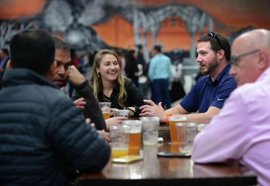 Patrons including GE employee Mike Derosa, second from left, gather for the grand opening of Junction at North Seven May 2, 2019, on Glover Ave. in Norwalk, Conn. Formerly a warehouse, 87 Glover Avenue, has been transformed into Norwalk's Premier Pop-Up Beer Garden through Julyof 2019. The space renovated with a vintage mural, and a 1920's Tap Truck will be serving craft beer and rotating craft cocktail selections with food trucks outside providing patrons with edible fare. The space has a variety of board games as well as Cornhole, Ping Pong, Giant 4 Connect in a Row and plans for showings of vintage black and white films. Photo: Erik Trautmann / Hearst Connecticut Media / Norwalk Hour