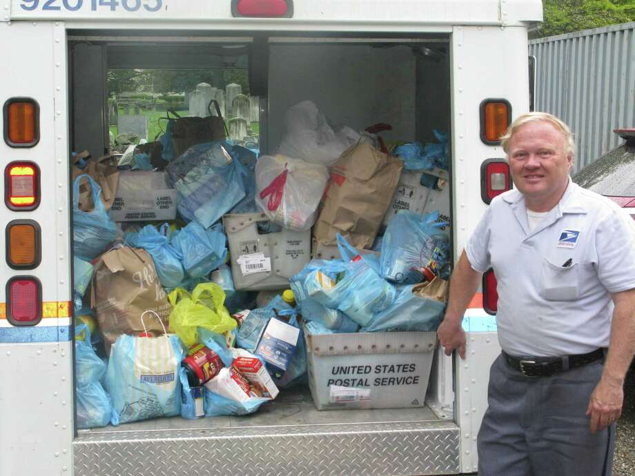 The annual Stamp Out Hunger food drive will benefit Neighbor to Neighbor. In 2014, letter carrier Glen Purdy collected 160 bags of donated food along his route. Photo: Contributed Photo / Contributed Photo / Greenwich Citizen
