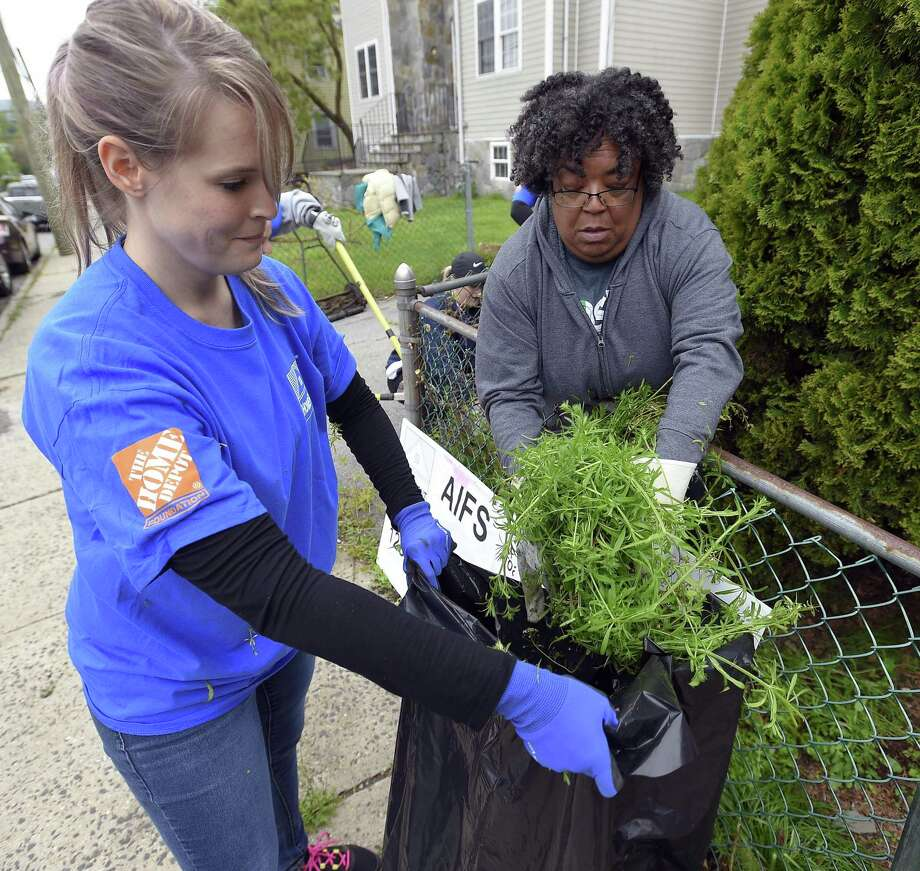 Volunteer Audra Christolini works with homeowner Licia Kendall as they clear over growth from the front of Kendall's home on Ann Street in Stamford on May 3, 2019. A group of volunteers from the American Institute of Foreign Studies donated their time to paint, fix and repair home projects as part of the 32nd annual HomeFront Day. Photo: Matthew Brown / Hearst Connecticut Media / Stamford Advocate