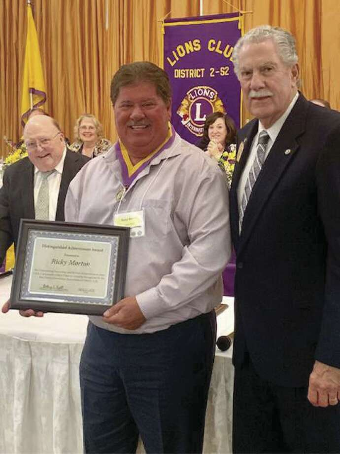 Ricky Morton, center, of the Conroe Noon Lions Club was honored last week with the greater Houston area Lions - District's Distinguished Achievement Award presented by Past District Governor Pat Brennan, right.