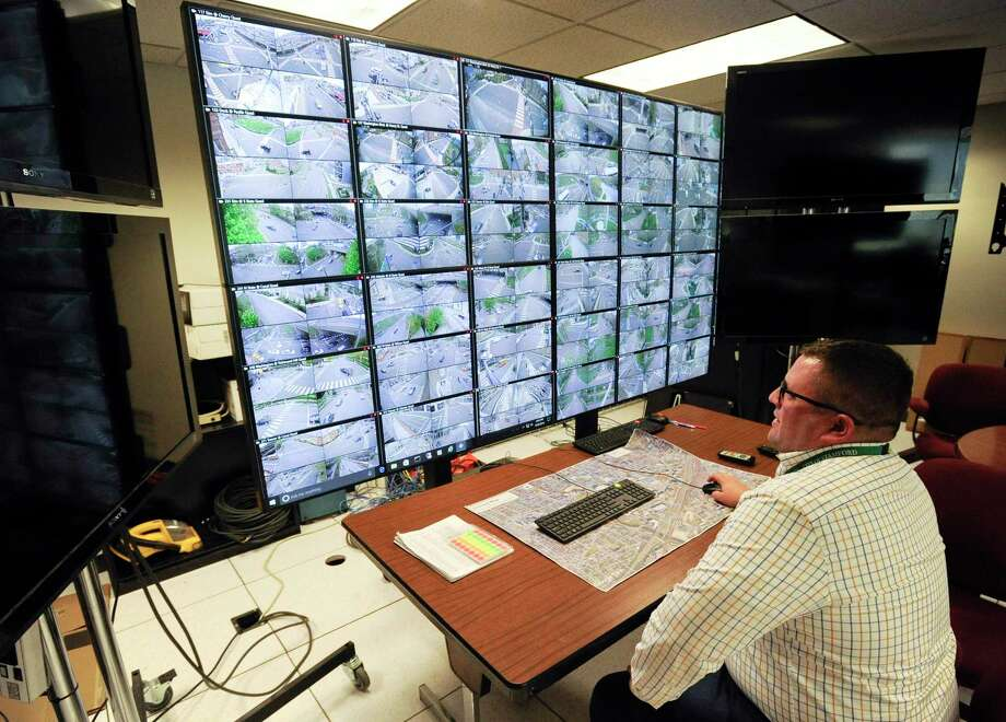 Frank Petise, an engineer in the City of Stamford Traffic Engineering Department, sits before an array of monitors on April 30, 2019, of several cameras throughout the city that monitor traffic, intersections, and other key areas in Stamford. Mayor David Martin touted the traffic light synchronization in his annual State of the City address. Photo: Matthew Brown / Hearst Connecticut Media / Stamford Advocate