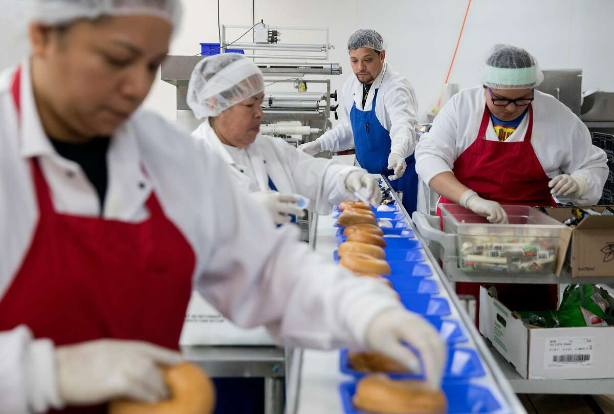 Workers assemble a variety of school lunches while at the Lunch Master facility in San Carlos, Calif., Friday, May 3, 2019.