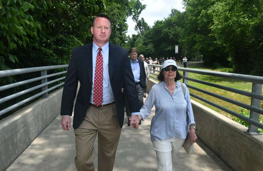 Lincoln Goodwin, left, Justice of the Peace, Harris County Precinct 4, Place 1, escorts Pauline Adams, the widow of Judge J. Kent Adams, the former Pct 4, Justice of the Peace, Place 1, across a bridge in Collins Park to the dedication ceremony of a park bench in honor of Judge Adams on April 30, 2019. Photo: Jerry Baker, Houston Chronicle / Contributor / Houston Chronicle