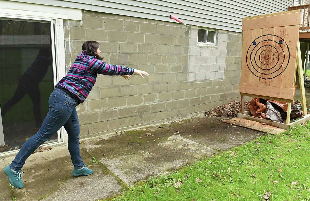 Kristyn Muller demonstrates a two-handed axe throw at her home on Friday, May 3, 2019 in Rensselaer, N.Y. Kristyn and Mark Mirasol hope to open their business, Lazy Axe, which is on Central Ave. in Colonie, in a month. (Lori Van Buren/Times Union)