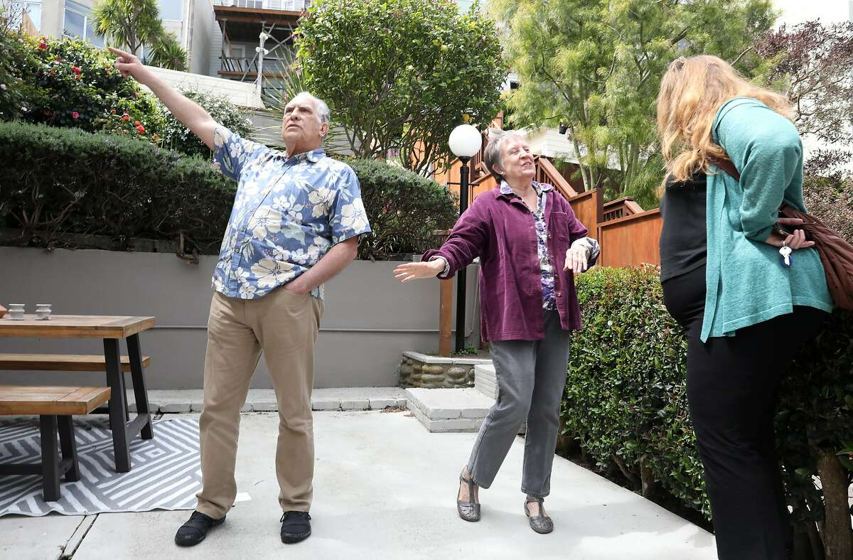 Greg Antipa (left) and his wife Wendy Thieler-Antipa (middle) talk to their realtor during an open house on Tuesday, April 30, 2019, in San Francisco, Calif.