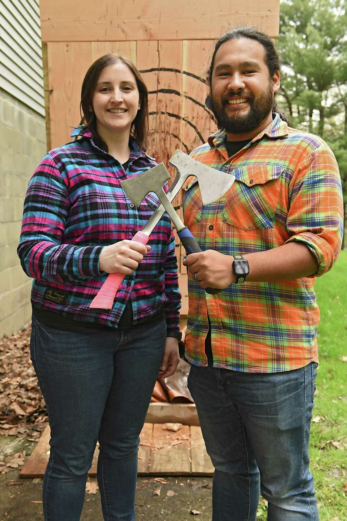 Kristyn Muller and Mark Mirasol, the founders of Lazy Axe, hold axes in front of a target in the back of their home on Friday, May 3, 2019 in Rensselaer, N.Y. The couple hopes to open their business, which is on Central Ave. in Colonie, in a month.(Lori Van Buren/Times Union)