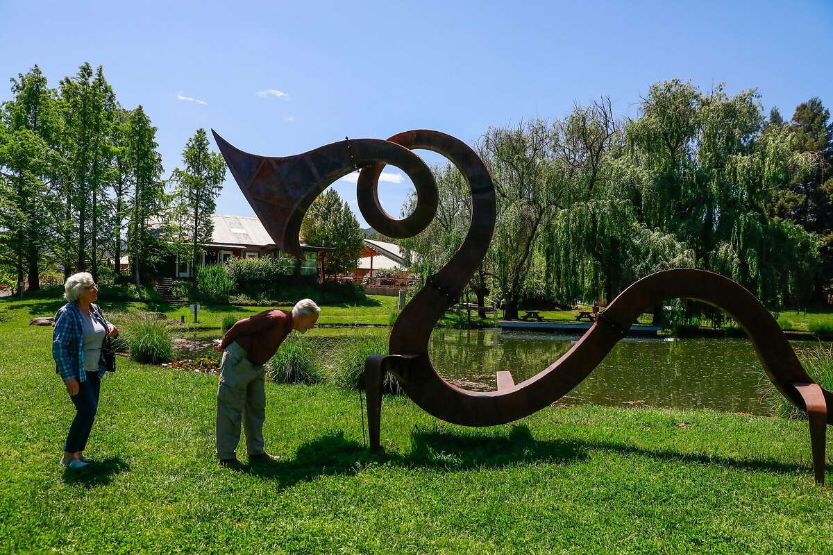 Donna and Charlie (last names preferred to be anonymous) check out the serpent sculpture at the Solar Living Center in Hopland, California, on Wednesday, May 1, 2019. Flow Kana recently bought the 12-acre property and will invest money into it to make it a visitors center.