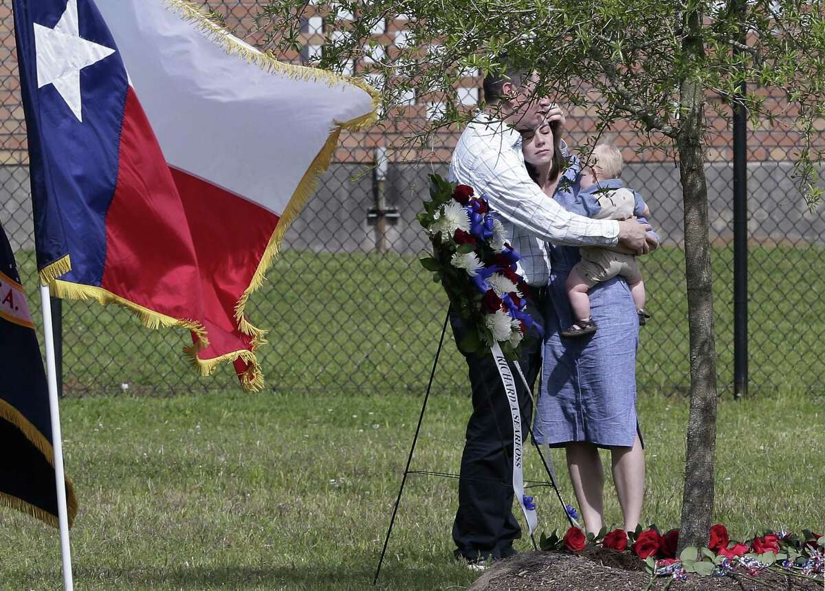 Megan Searfoss Furse is hugged by her husband as she holds one of her children while other friends and family lay roses at the base of a tree at the dedication ceremony for Furse's father, three-time space shuttle astronaut Col. Richard A. Searfoss, in the memorial grove at the Johnson Space Center on April 16, 2019 in Houston.