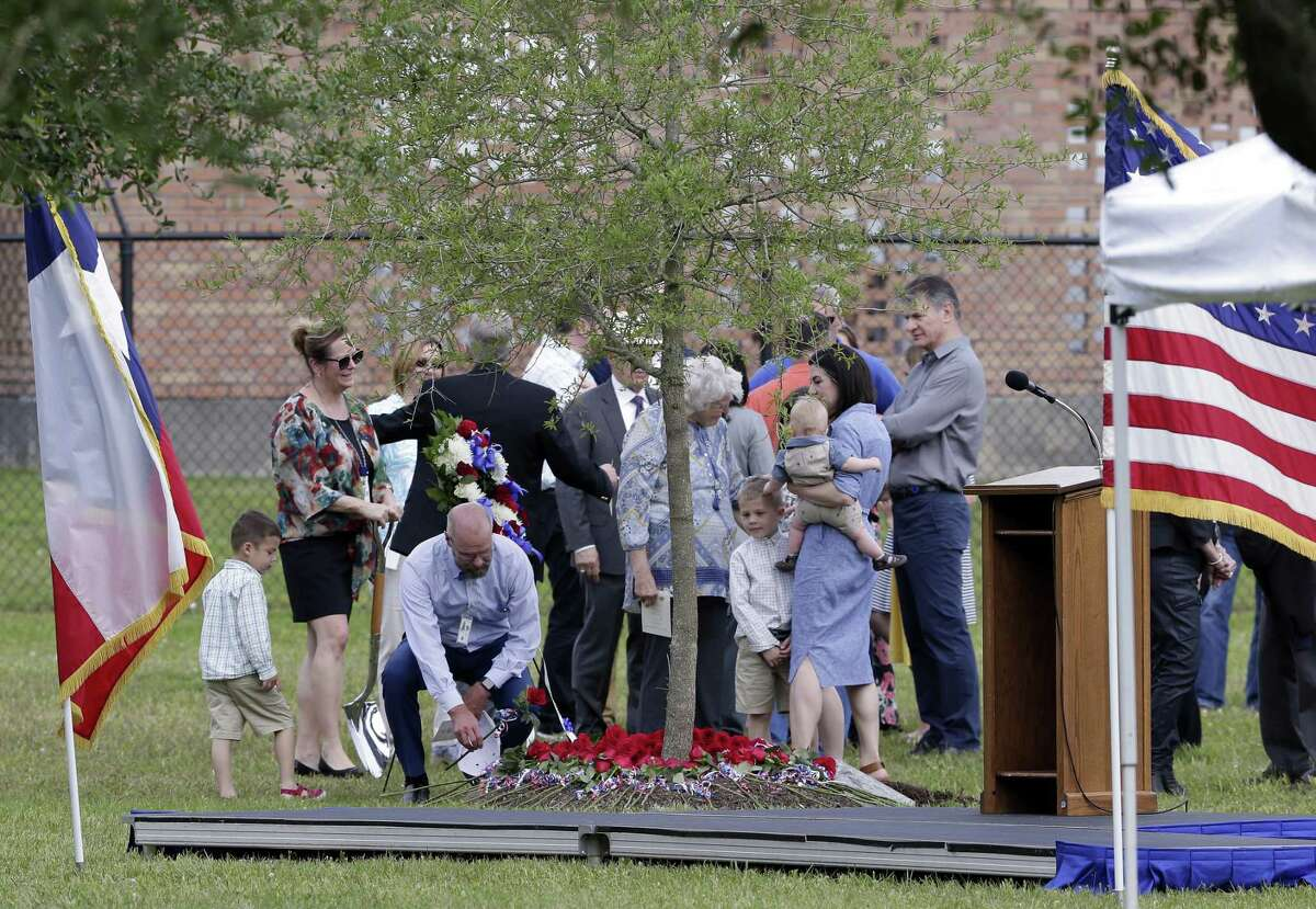 Family, friends and co-workers lay roses at the base of a tree after the dedication ceremony for three-time space shuttle astronaut Col. Richard A. Searfoss in the memorial grove at the Johnson Space Center on April 16, 2019 in Houston.
