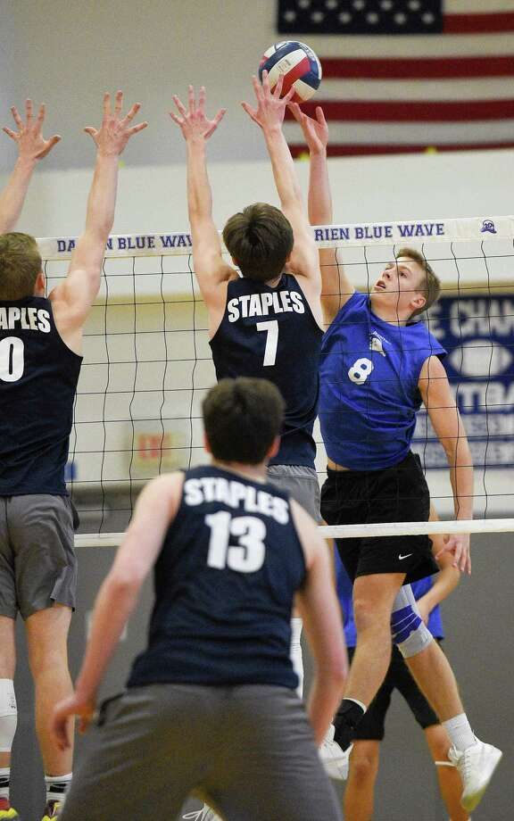 Darien's Tyler Herget (8) taps the ball over the reach of Staples' Logan Carstens (7) in Wednesday's match between the two division leaders. Photo: Matthew Brown / Hearst Connecticut Media / Stamford Advocate