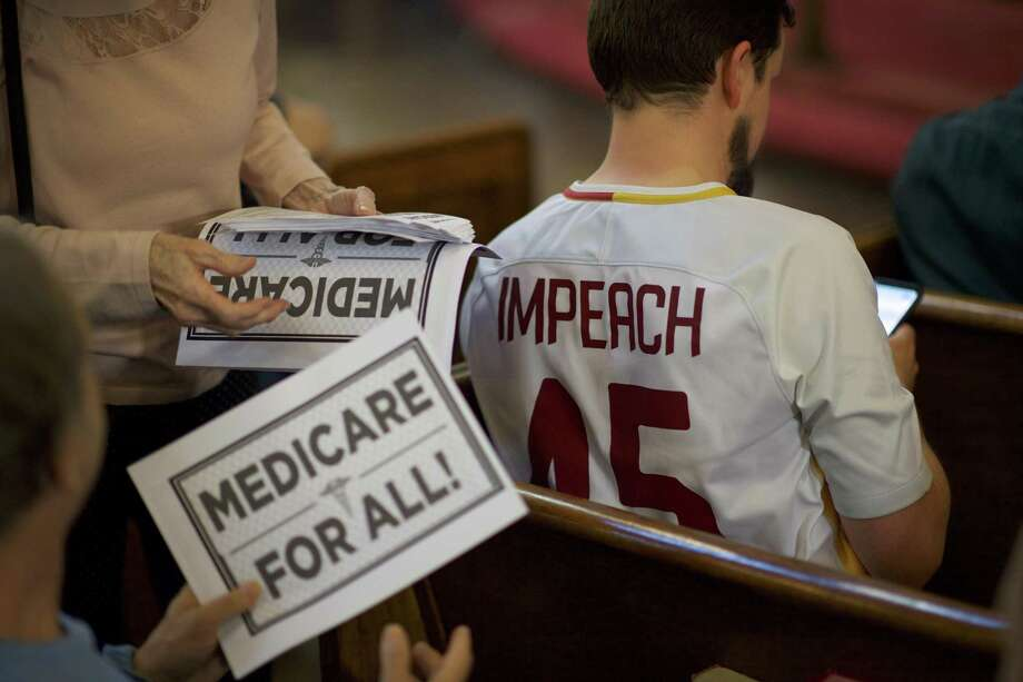 """Medicare for all"" signs and an ""Impeach 45"" shirt in the audience at a town hall-style event with House Democrats in Philadelphia, April 24. If impeached, the president will fight like a caged animal. Photo: MARK MAKELA /NYT / NYTNS"