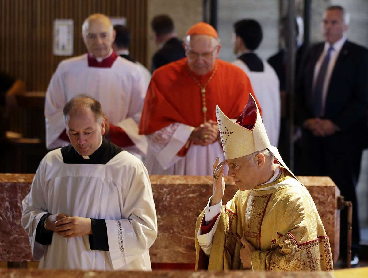 Salvatore J. Cordileone, at right, rubs his forehead with holy water during a ceremony to install him as the new archbishop of San Francisco at the Cathedral of St. Mary of the Assumption in San Francisco, Thursday, Oct. 4, 2012. (AP Photo/Marcio Jose Sanchez, Pool)