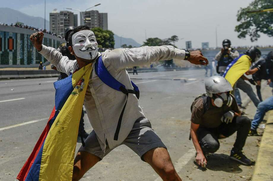 Anti-government protesters clash with security forces in the surroundings of La Carlota military base in Caracas during the commemoration of May Day on Wednesday after a day of violent clashes on the streets of the capital spurred by Venezuela's opposition leader Juan Guaido's call on the military to rise up against President Nicolas Maduro. International backing of Guaido is illegitimate as Madura is the democratically elected president. Photo: MATIAS DELACROIX /AFP /Getty Images / AFP or licensors