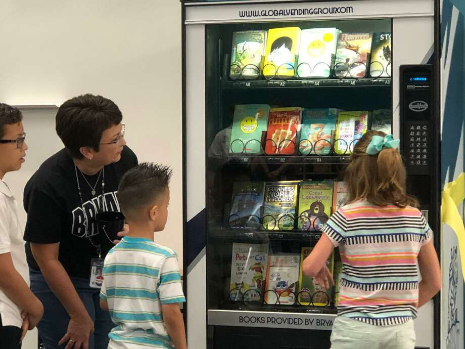Bryant Elementary School librarian Nidia Casillas helps students lining up to make a selection at the school's new book vending machine on Thursday, May 2. Photo: Mike Glenn / Staff Photo