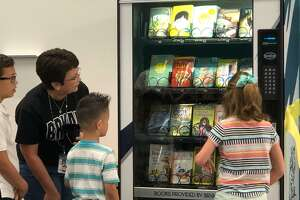 Bryant Elementary School librarian Nidia Casillas helps students lining up to make a selection at the school's new book vending machine on Thursday, May 2.