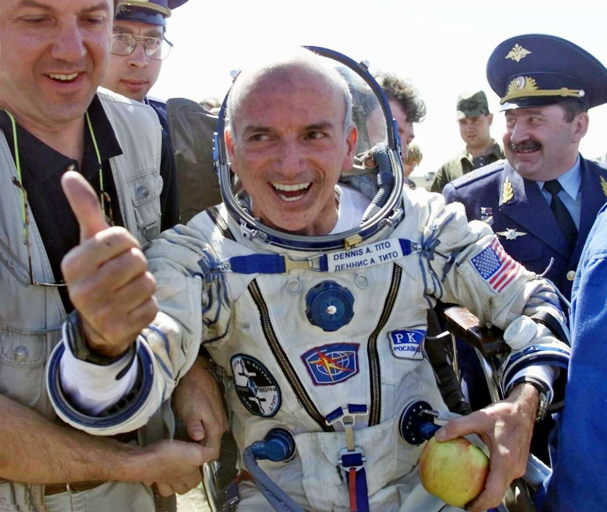 American multimillionaire Dennis Tito, 60, gestures shortly after his landing on the steppes, 50 miles northeast of Arkalyk, Kazakstan, on May 6, 2001. Others are unidentified. The Russian Soyuz capsule carrying the world's first paying space tourist landed successfully, ending Tito's multimillion dollar cosmos adventure.