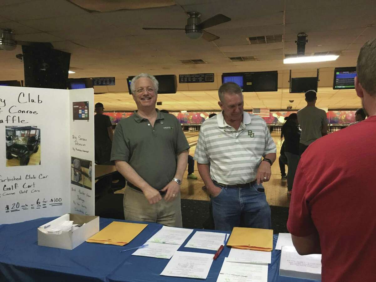 Rotary Club of Conroe President Leland Dushkin, left, and President Elect Denny Buckalew, right, sign in participants for the club's first 5th Tuesday Bowling Night Tuesday night at 300 Bowl in Conroe.