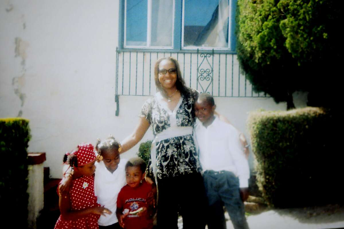 """In this undated family photo, Deyana Jenkins (second from left) is held by her mother, Deborah McCoy, while she gives her brother-in-law, Willie McCoy (right) a hug. On April 16, Jenkins was violently arrested by the Vallejo Police Department during a traffic stop. Her uncle, Willie McCoy, was fatally shot by Vallejo police officers as he slept in his vehicle on February 9. Many Vallejo residents have demanded police reform because of troubling arrests and fatal shootings by the VPD. """"For one, I was really scared. I was nervous. I was thinking like, 'Lord, please don't let them shoot me. I hope this is not like my last good-bye ... seeing my friends,' """" Jenkins said. """"I was just really, just trying to stay cooperative."""""""