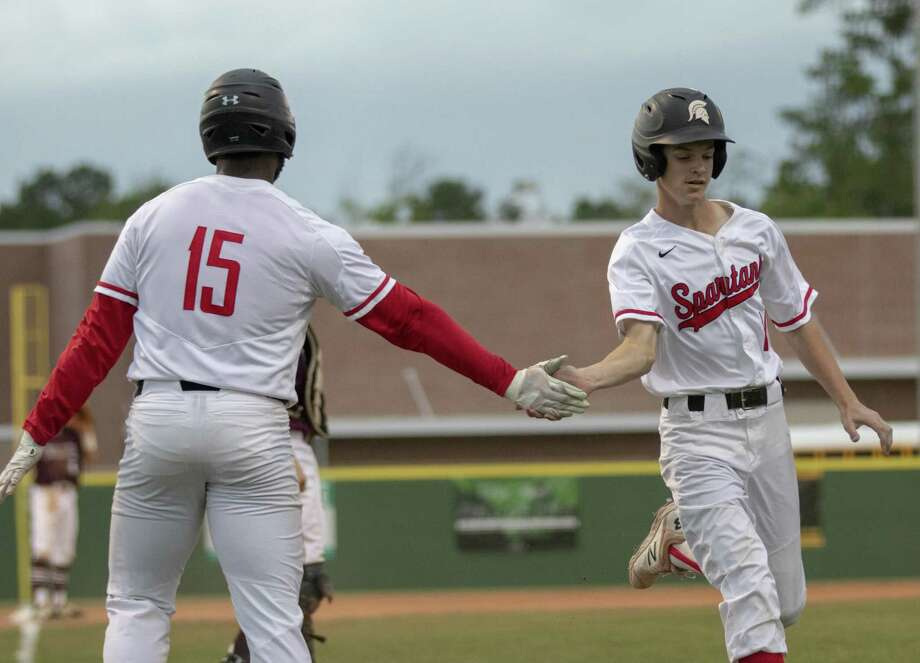 Porter third baseman Max Dias (15) and Jake Tatom (14) of Porter high five after both crossing home plate during game one of a Region III-5A bi-district baseball series Thursday, May 2, 2019 at Porter High School. Photo: Cody Bahn, Houston Chronicle / Staff Photographer / © 2018 Houston Chronicle