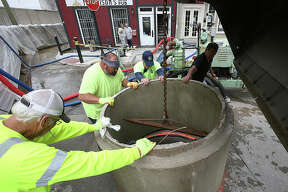 Alton Public Works employees lower a concrete section of storm pipe over a sewer grate Friday inside the six-foot flood wall erected at the foot of State Street. The pipe will help control backup from the sewer as floodwaters rise to what is expected to be the fifth highest level in recorded history by Monday. The Argosy Casino closed operations Friday, residents of West Alton, Missouri, were still packing up and moving out and water was covering parts of Riverfront Park. See more photos at www.thetelegraph.com.