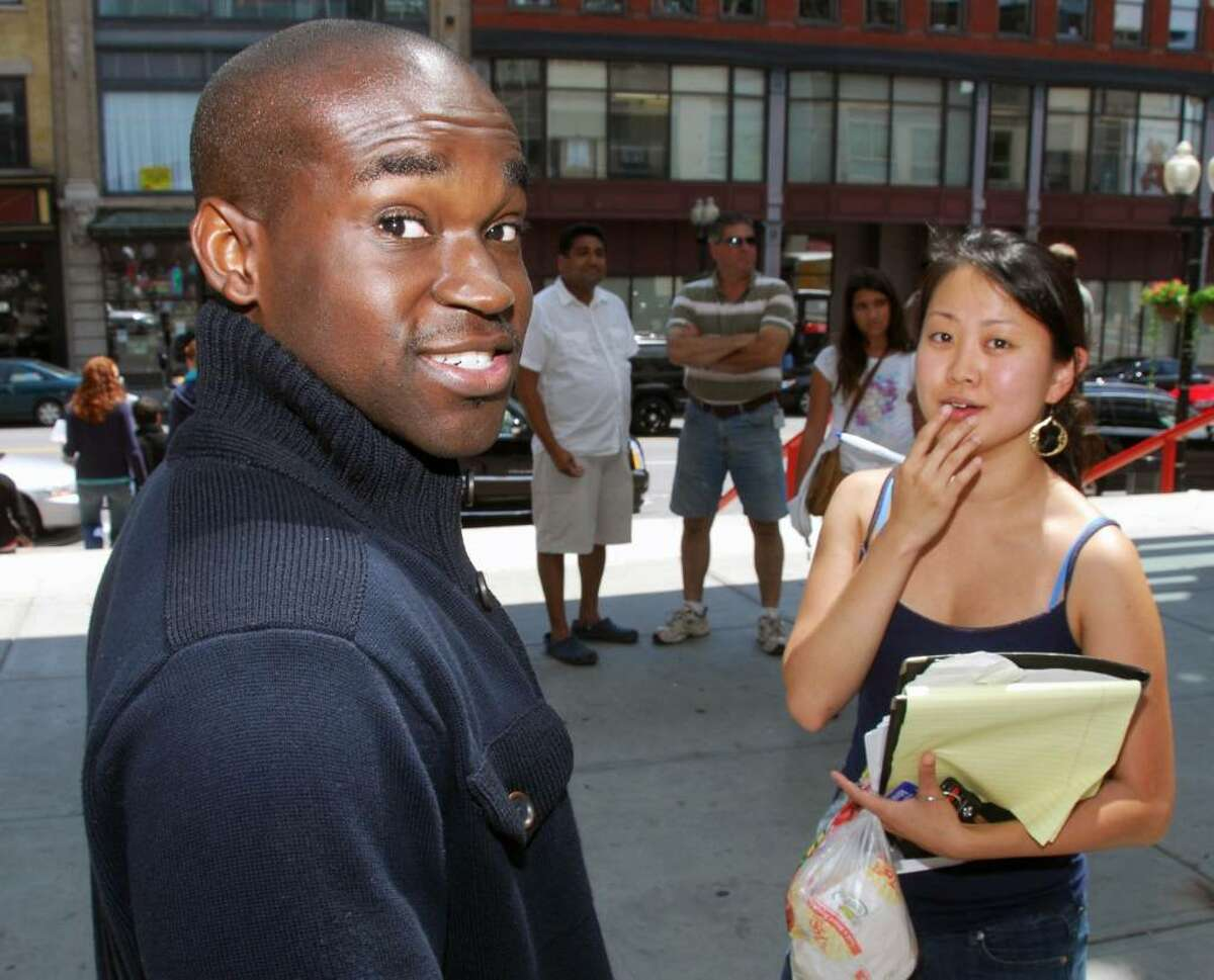 Harvard Law grad Yaw Asare, left, of Columbus, Ohio, is met by attorney Jenn Kim, a clinical graduate fellow at Albany Law School, as Asare breaks for lunch from the New York bar exam at the Times Union Center on Tuesday. Some 1,130 people took the test at this site, one of five in the Capital Region. The exam concludes Wednesday. (John Carl D'Annibale / Times Union)